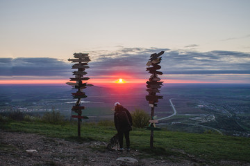 Girl stroking dog on top of mountain looking at the sunset and the plain, next to the wooden signs of the cities.