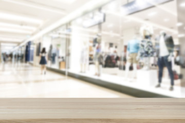Empty top wooden table and blurred on blur shopping mall luxury and derpartment store for background