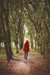Woman in red coat walking in the forest