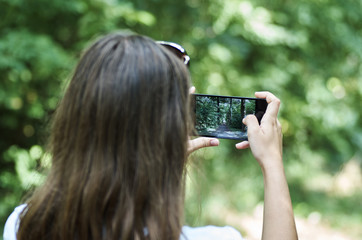 A young girl by mobile phone is photographing a landscape with a forest