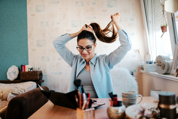 Woman doing hair care, tying hair.