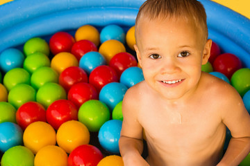 cute boy in pool with colorful balls