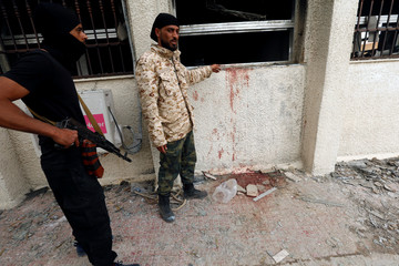 Security personnel stand at the site of a suicide attack on electoral commission in Tripoli
