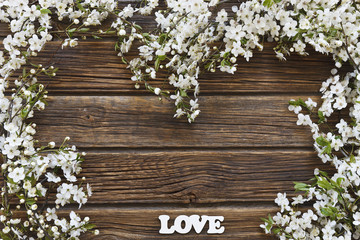 Close-up photo of Beautiful white Flowering Cherry Tree branches with  white letters love. Wedding, engagement or betrothal concept on vintage wooden background. Top view, greating card.