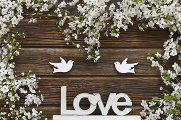 Close-up photo of Beautiful white Flowering Cherry Tree branches with two wooden birds and letters love. Wedding, engagement or betrothal concept on vintage wooden background. Top view, greating card.