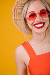 Adorable smiling blonde woman portrait on yellow background. Heart shaped pink sunglasses. Happy summer mood moments. Vertical photo