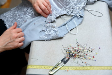 A woman embroidering a handmade dress. Today, tailoring can be called as an artistic profession.