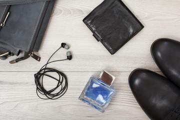 Pair of black leather men's shoes, leather shoulder bag for men,  men's cologne, headphones and purse on wooden background