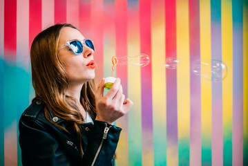 Happy young blonde woman in a colorful background playing with soap bubbles