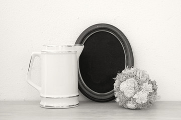 A frame for photography, a white jug, a bouquet of flowers, a melon. Place for text. Black background. Mock up.