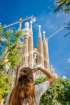 Girl tourist near Sagrada Familia. Architecture Antonio Gaudi. A woman with long hair and a backpack is traveling around Barcelona. Tourist in Spain. Walking tour