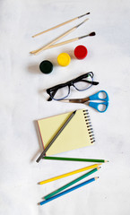 A pile of various stationery on table, notepad, colored pencils, ruler, marker, planer, space for text. Delicious school lunch box, sandwich and fruit. The concept of preparing children