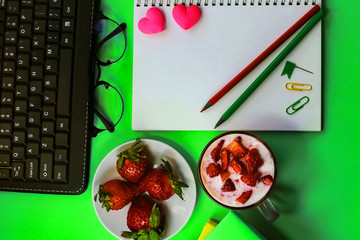 office workspace. Strawberry. yoghurt with strawberries. artificial flowers, stationery, glasses, keyboard. toned background