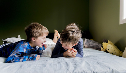 Cheerful brothers lying on bed at home