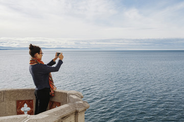 Woman photographing sea with smartphone while standing on terrace