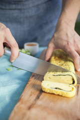 Midsection of female chef cutting baked pastry item in commercial kitchen