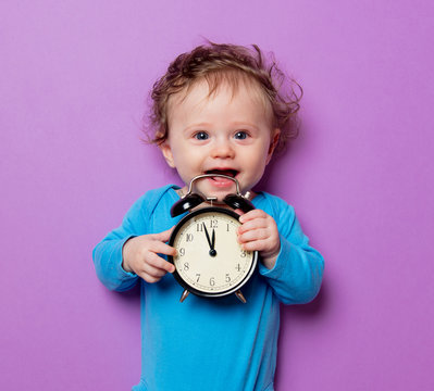 little infant baby with alarm clock lying on purple background
