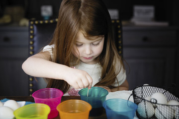 Cute girl coloring Easter Eggs on table at home
