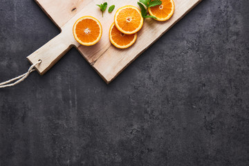 Flat lay of fresh citrus fruits, half cut orange slices on cutting board on black stone background. Horizontal top view with copy space.
