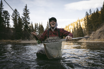 Cheerful man screaming while fishing in river against sky at forest