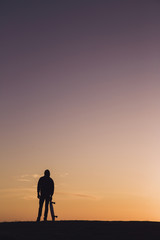 Silhouette man with skateboard standing against dramatic sky during sunset