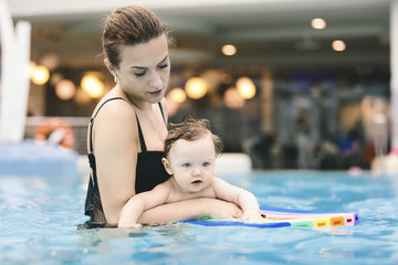 Woman carrying cute baby girl while swimming in pool