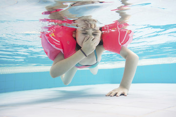 Girl wearing water wings swimming underwater in pool