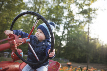 Baby boy sitting on tractor at pumpkin patch