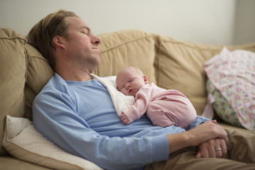 Father with baby girl sleeping on sofa at home