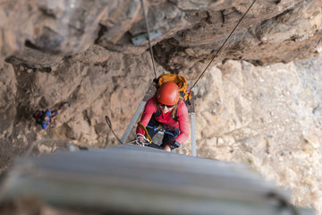 High angle view of female hiker wearing helmet while climbing on rope ladder amidst mountains