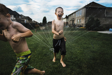 Shirtless brothers running by sprinkler in lawn