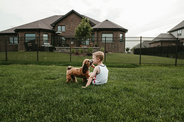 Rear view of boy kissing dog while sitting on grassy field against sky at park
