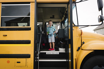 Portrait of boy with backpack standing in school bus