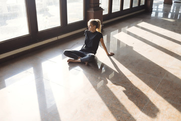 Thoughtful young woman sitting on tiled floor while looking through window