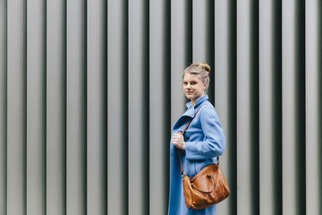 Side view portrait of confident young woman wearing trench coat while carrying purse against shutter in city