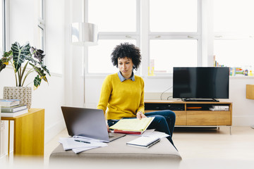 Serious businesswoman using laptop computer while sitting in office