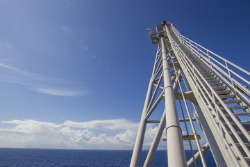 Low angle view of crane on oil rig against blue sky during sunny day