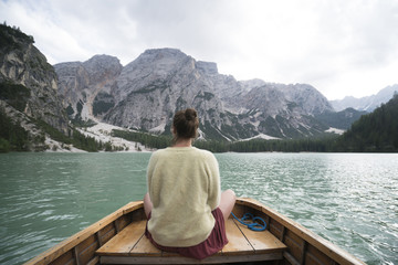 Rear view of woman sitting in boat on river amidst mountain against sky