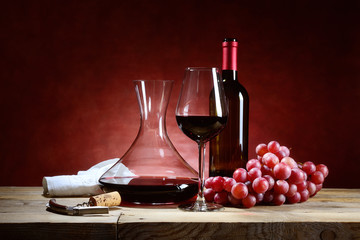 Red wine glass with bunch of grapes and decanter