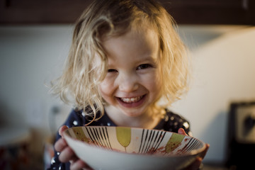 Close-up portrait of happy girl holding bowl at home