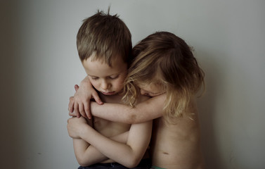 Shirtless sister embracing sad brother by wall at home