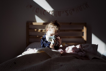 Girl embracing doll while sitting on bed in darkroom at home