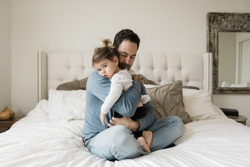 Portrait of sad daughter embraced by father on bed at home