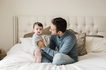 Portrait of cute son with father on bed at home