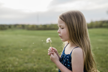Side view of girl blowing dandelion flower on grassy field