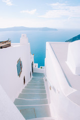 Narrow street on the island of Santorini with steps going down to the sea.