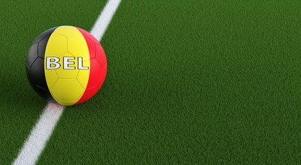 Soccer ball in Belgian national colors on a soccer field. Copy space on the right side - 3D Rendering