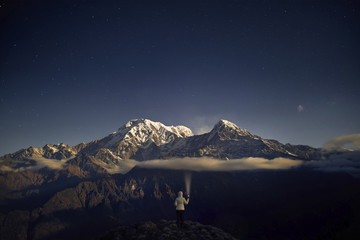 Rear view of tourist holding flashlight while standing on mountain against sky at night