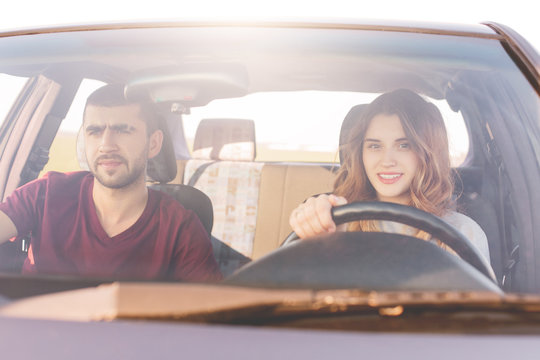 Couple travelers reach destination at car: beautiful smiling woman at wheel teaches to drive, her husband sits at front seat, controls everything. Girlfriend, boyfriend spend time together, have trip