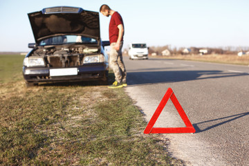 Car breakdown concept. Helpless man driver stands near brocken auto with opened hood, has problems with engine, can`t drive any more, warns other drivers with warning red triangle sign on road Wall mural